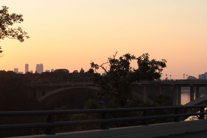The sky glows orange, as the sun dips below the horizon. From Mississippi River Boulevard looking northeast at downtown Minneapolis.