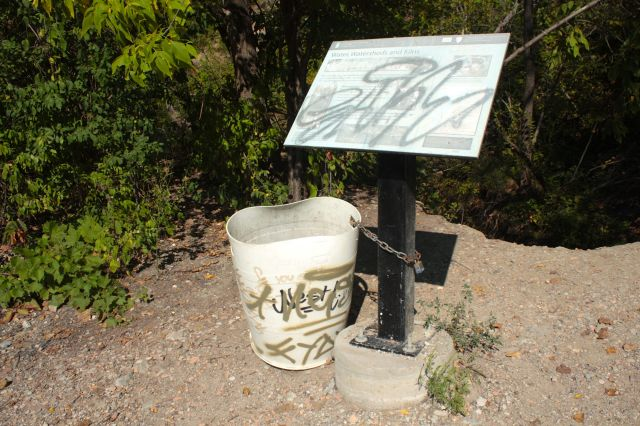 An interpretive sign and a garbage bucket, both clearly vandalized.