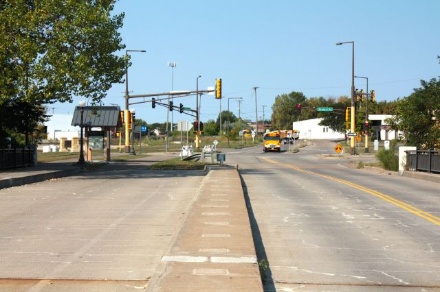 Looking west at the intersection of Shepard Road and Randolph Avenue. The school bus awaits a green light to turn left onto Shepard. On the left, the green roofed structure is a new interpretive display of area history.