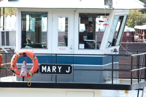 """The pilot of the tug """"Mary J"""" concentrates on the two barges he's pushing."""