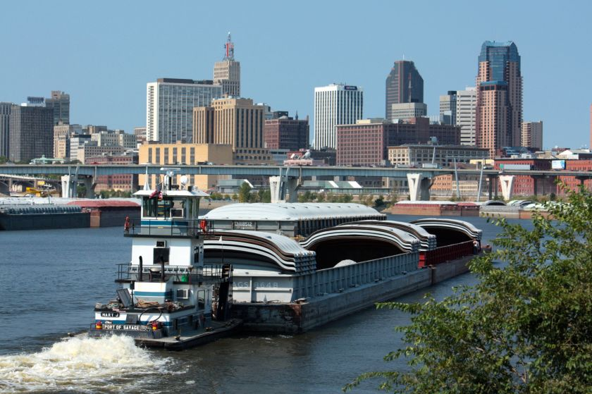 """The """"Mary J"""" moves two barges upriver. Downtown Saint Paul is in the background."""