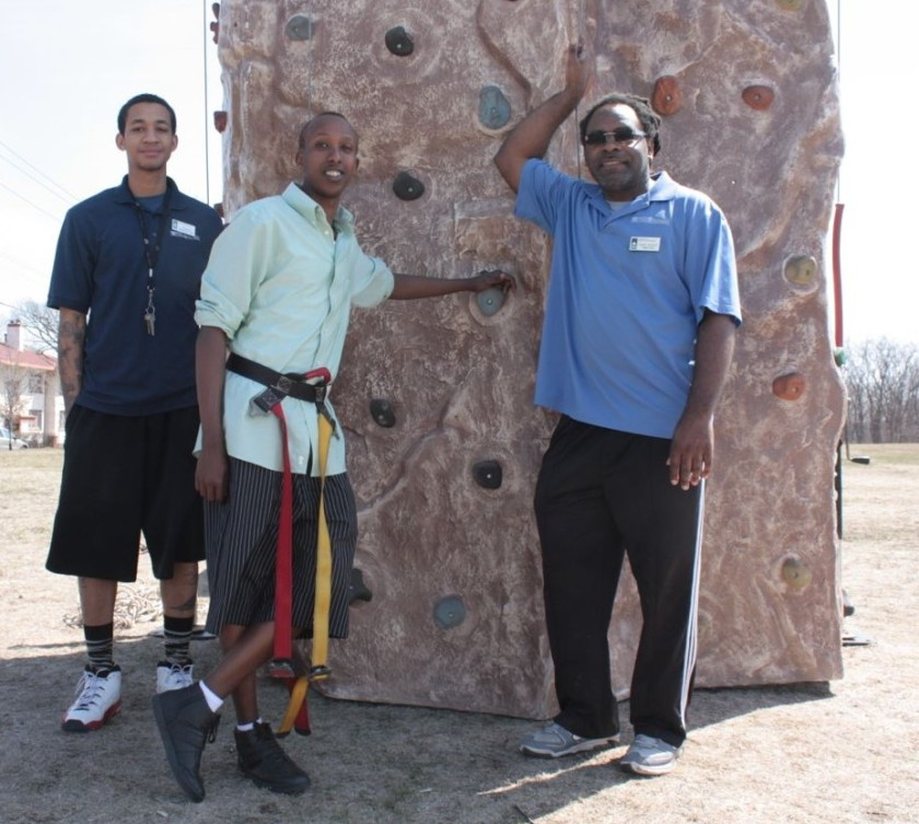 Alex Glass and his assistants, Jordan and Askar, in front of the portable climbing wall.
