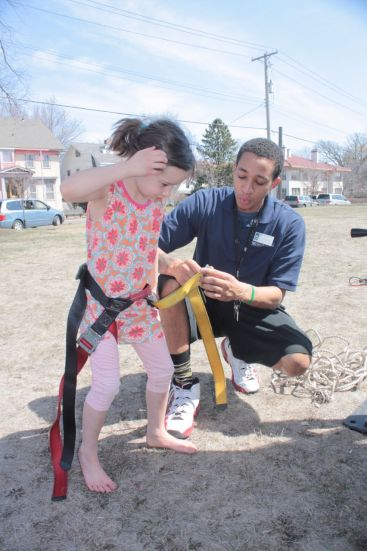 Jordan attaches harness on a young climber.