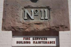 The original Fire Station 11 carving and below it, the current sign.