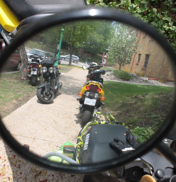 Several scooters are reflected in the mirror of another.