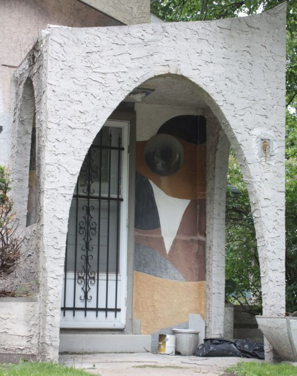 The entrance to 1476 Iglehart features imaginatively painted stucco and a bubble window.