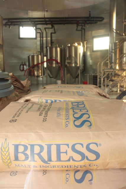 The bags of malt await the start of the next batch of beer.)