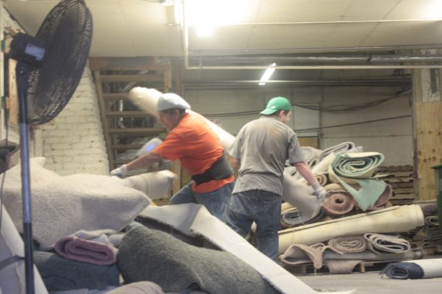 Workers begin the recycling process by picking up carpet and moving it to a machine that determines its composition.