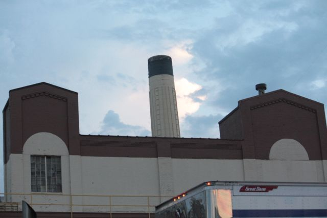 The roofline of one of the older buildings and the smokestack that towers above the plant.