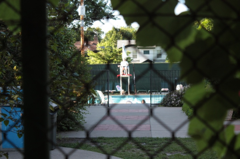 The tennis club also has a swimming pool which is somewhat obscured by thick bushes.