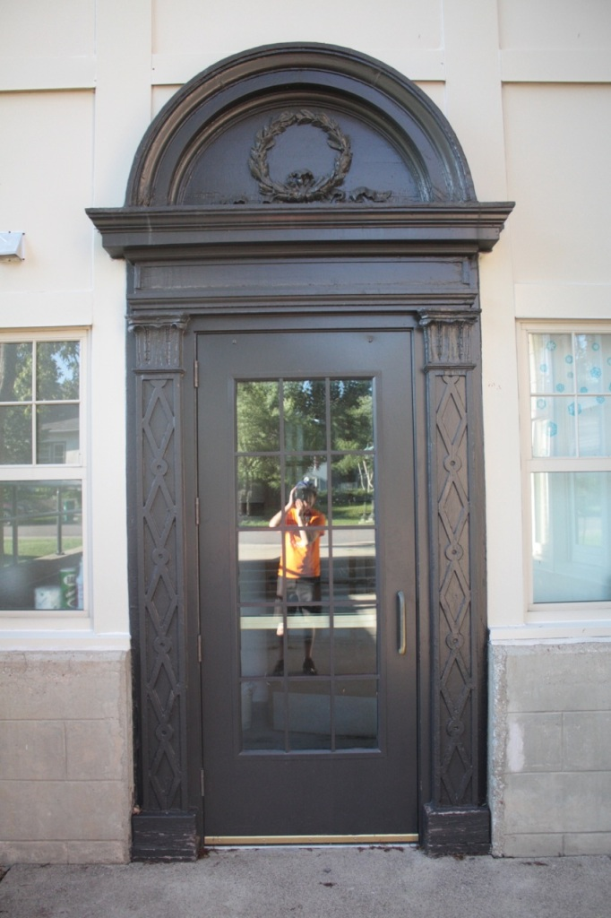 This entrance to the school features ornamental flourishes  around the do and yours truly reflected in the window.