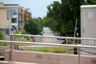 Emerald Avenue, the boundary between Saint Paul and Minneapolis, as seen from University Avenue. The silver railings and control box in the foreground are part of the Light Rail on University.