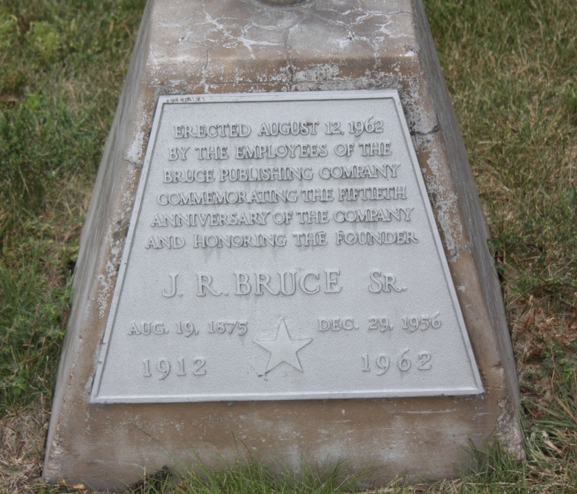 a plaque placed on the flagpole at the aforementioned Bruce Publishing Company remains years after the business moved on.