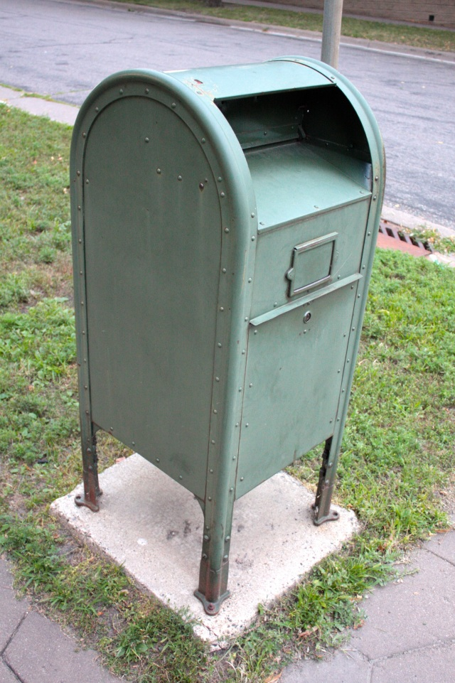 This is a mailbox for USPS mail carriers. It's called a relay box and is used by letter carriers to leave packages and mail for later delivery by another postal worker. The elements have faded this relay box from its original olive drab color.