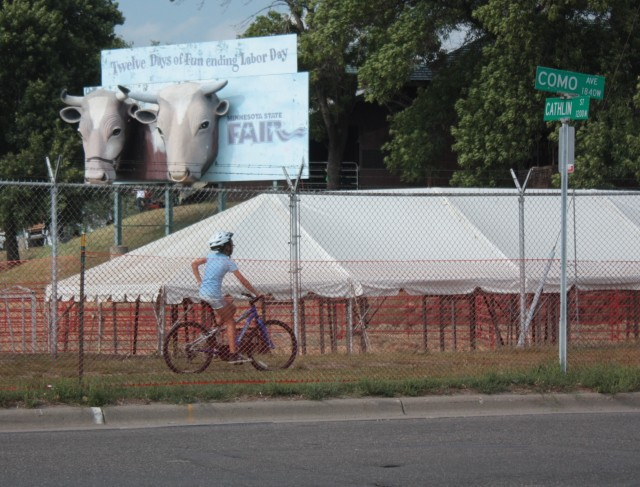 A biker moooves past a State Fair sign on Como Avenue.