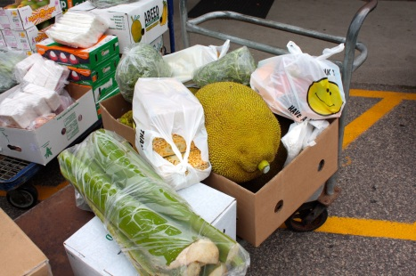 A couple of cart loads of exotic produce await loading into a nearby vehicle.