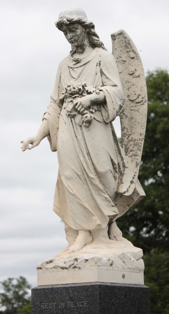 This angel, guardian of the tomb, sits atop the grave marker of the James family.