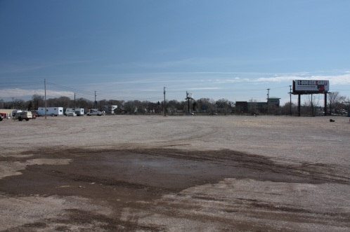 The view south across the large parcel of land that stretches from Midway Center to St. Anthony Avenue. Light rail construction equipment is on the left and the homes and building in the background are on Concordia Avenue, on the south side of the I-94 corridor.