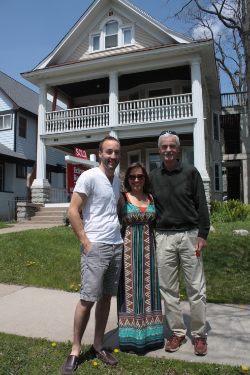 Tony Pavelko and Gina DiMaggio, stand in front of the triplex they're buying with the current homeowner, Bob.
