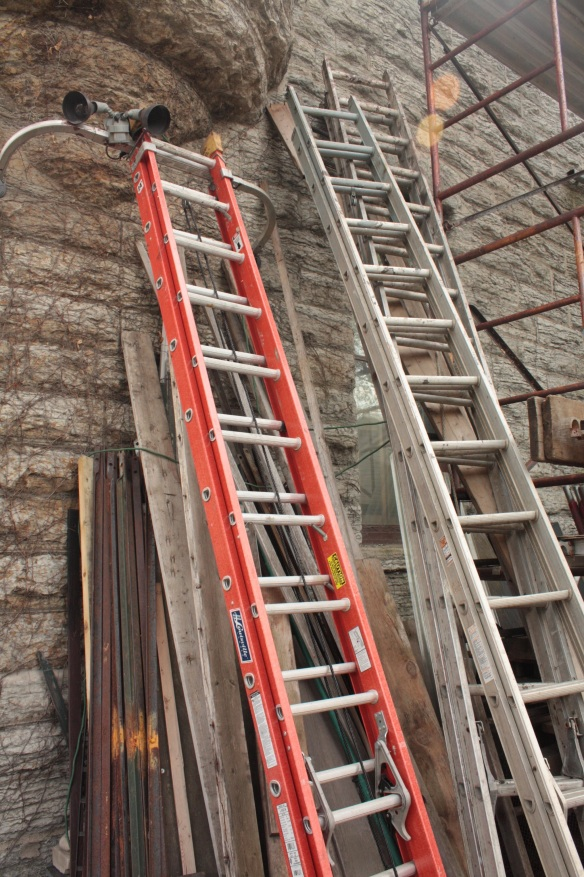 Ladders are stacked on a back wall of the house as  renovation.
