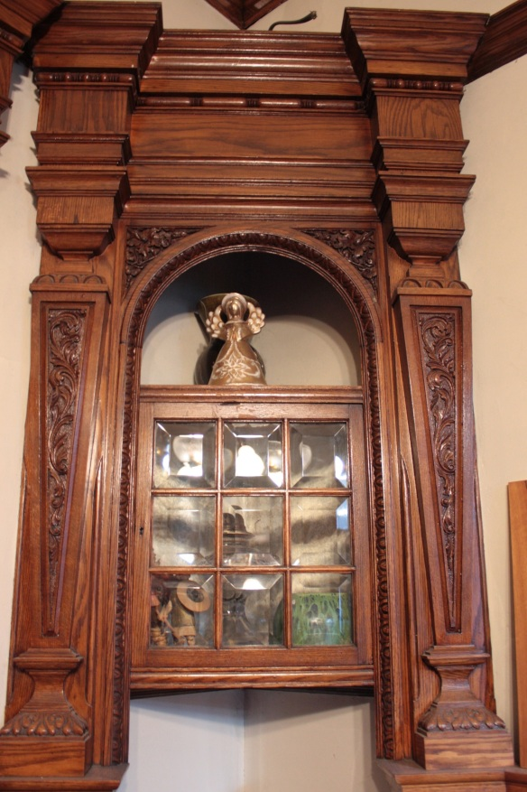 A cabinet and intricately carved woodwork in the parlor.