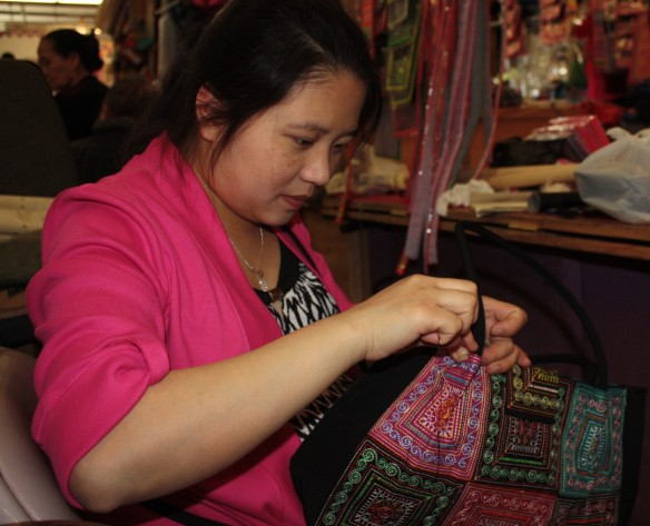 In a booth at the Market a woman stitches a traditional Hmong outfit.