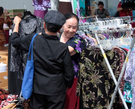 Two women discuss the purchase of a dress at Hmongtown Marketplace.