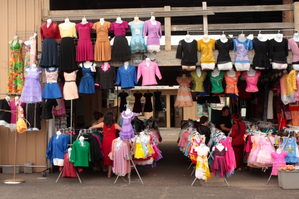 The variety of colors on dresses and tops makes a rainbow look plain.