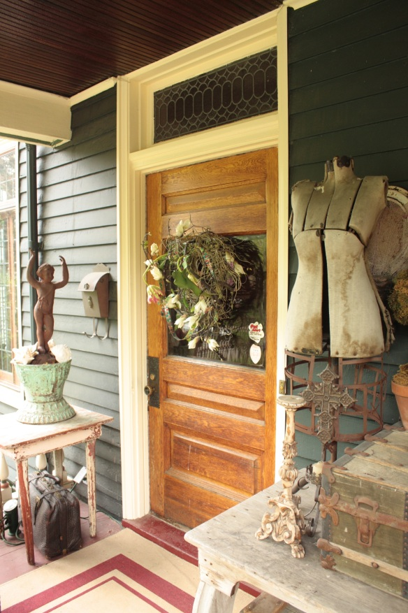 A wreath and mannequin from yore decorate the home's entrance.
