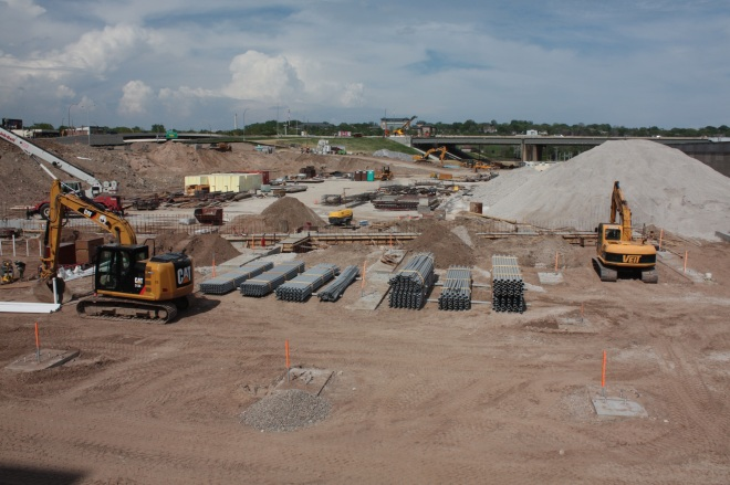 Heavy equipment, piles of dirt and some pipe sit ready to resume work.
