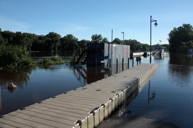 Water laps at the temporary pier, installed presumably to allow boaters access while the permanent piers were under water. Notice the street light, two buildings in the background and the bushes on the left are all surrounded by water.