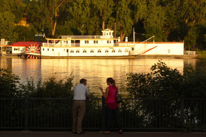 Two people shoot the breeze as the Mississippi rolls by.