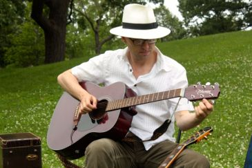Artistic Director Joseph Papke tunes his guitar as show time grows near.
