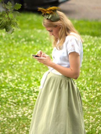 The actress in period clothing looking at her smartphone is an odd dichotomy.