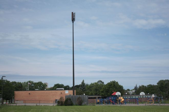 Cell phone coverage is important but putting a large tower on the playground of a school? I bet money factored in to this phone tower reaching skyward at Maxfield Elementary.