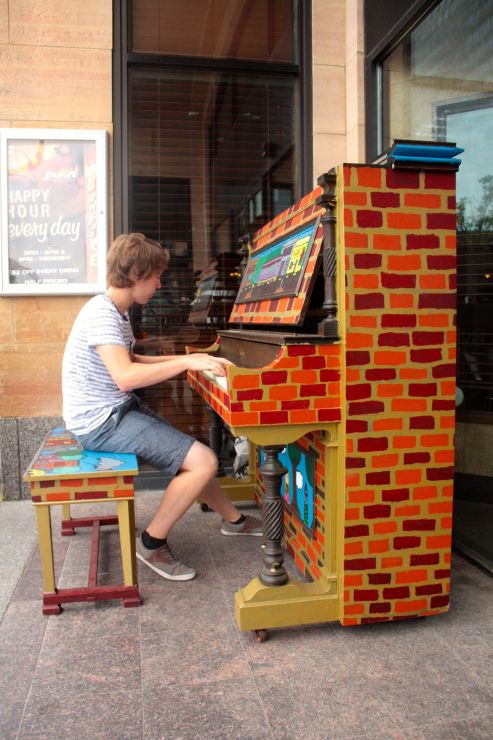 "Parker Zachman plays one of the ""Pianos On Parade"" (POP) keyboards at Victoria Crossing."