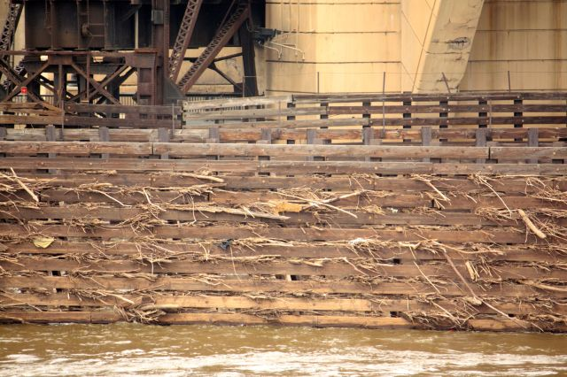 Flooding in the spring left tree branches and other debris in the wood fence that separates the Mississippi navigational waterway from another channel.