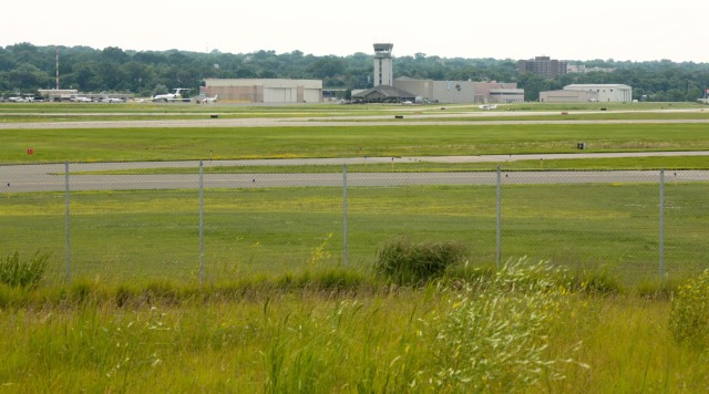 The north-south runway is in the foreground and the control tower and private hangers can be seen in the background.