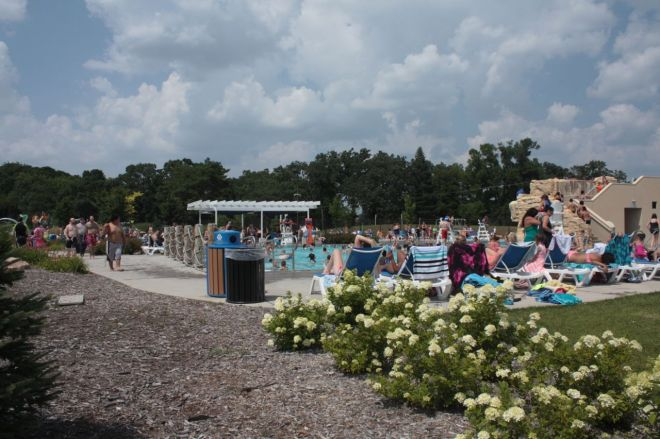 """The """"aquatic climbing wall"""" and zip line (right) and oodles of lounge chairs are a couple of the reasons for the pool's popularity."""