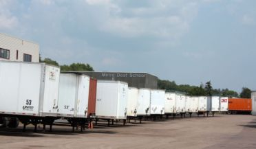 Trailers line one side of the parking lot at 1102 Snelling Avenue. In the background you can see the Metro Deaf School and Hmong College Prep.