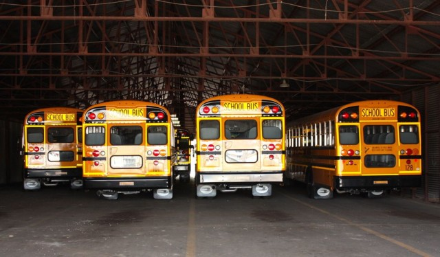 Shiny new buses sit in the garage awaiting the start of school in about a month.