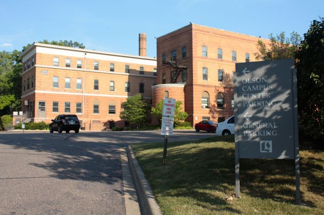 The sign says Olson Campus Center parking but the building is the back of Brockman Hall on Como Avenue. Brockman has a collection of uses, including faculty and staff offices, classrooms and dorm rooms.