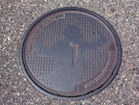 "The orchestra director manhole cover is one of at least four designs created through the ""Hand In History"" outreach program, sponsored by the City of Saint Paul and the department of public works. Another of the designs sits near the intersection of Summit and Macalester in the Mac-Groveland neighborhood."