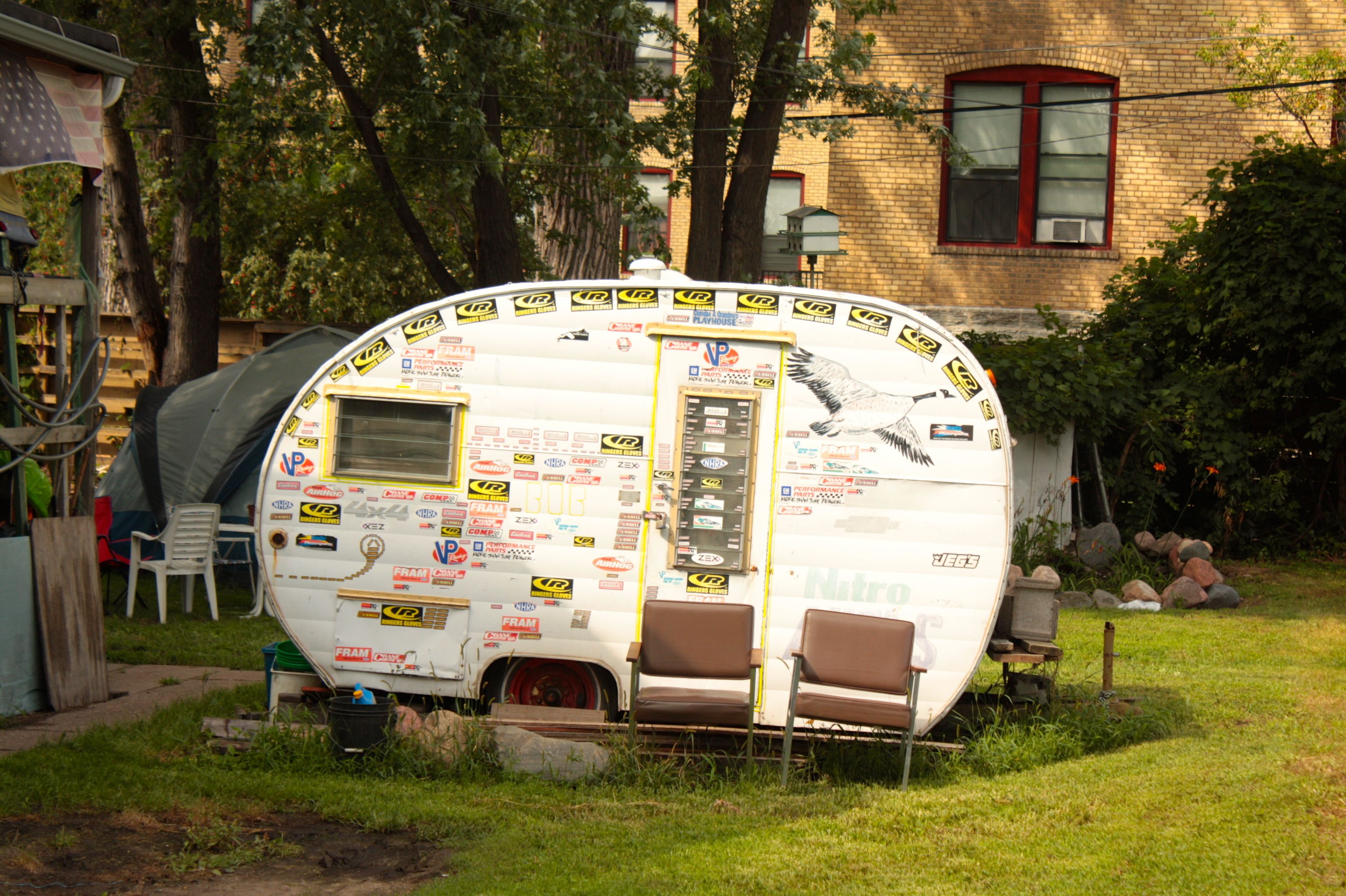 The sticker-covered trailer and two 1970s-era chairs create the perfect atmosphere for relaxing outside.