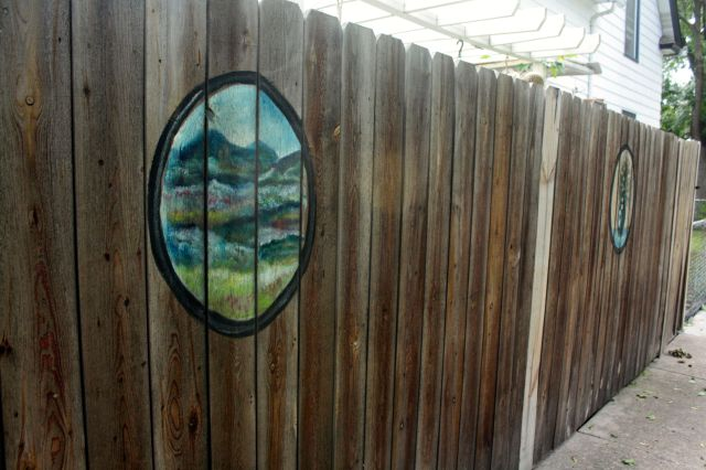 The landscape and still life decorate the fence of the home at Blair and Asbury.