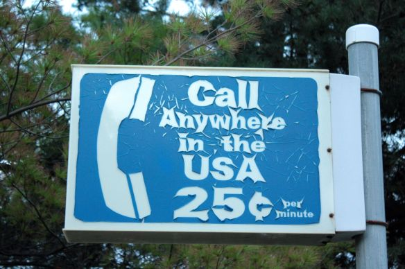 "The payphone is long gone but this once-common sign still hangs on a pole above the parking lot at Mickey's ""By Willie."""