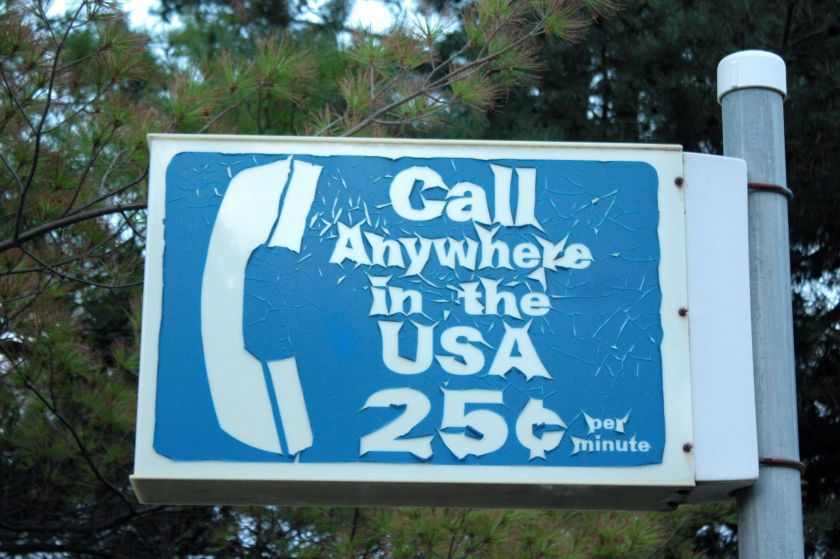 """The payphone is long gone but this once-common sign still hangs on a pole above the parking lot at Mickey's """"By Willie."""""""