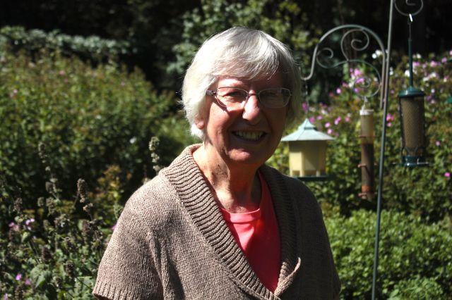 Carol Sturgeleski stands in her back yard amongst the flowers and bird feeders.