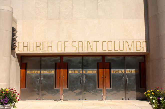 The steel doors and above them, the stunning gold lettering are strongly set off by the white stone building