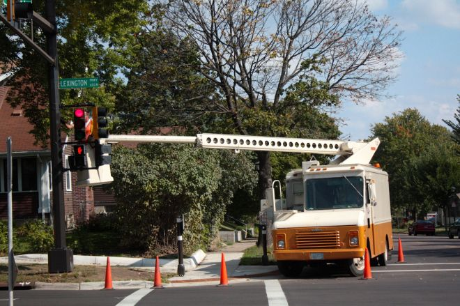 Kerry works on the traffic light overhanging Lexington. The only place he can park the bucket truck is in the street.